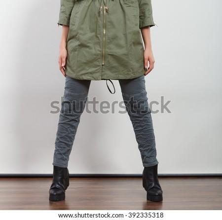 Closeup of woman girl in dark green khaki coat and winter boots posing in studio. Autumn fall fashion. - stock photo