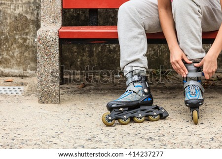 Closeup of woman girl putting on roller skates outdoor.
