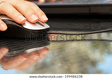 Closeup of woman hand holding mouse - stock photo