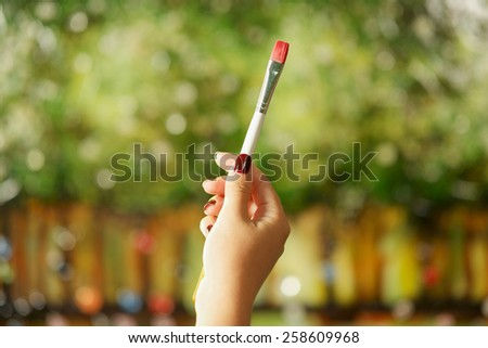 Closeup of woman hand holding painting brush and studying composition of picture on canvas - stock photo