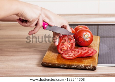 Closeup of woman hand preparing tomato in the kitchen. - stock photo