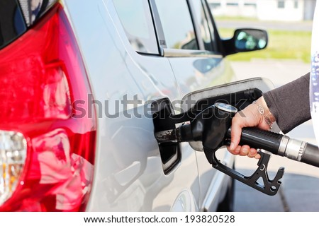 Closeup of woman hand pumping gasoline fuel in car at gas station.  - stock photo