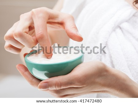 Closeup of woman hands holding bowl with nourishing mask; skincare and haircare concept - stock photo