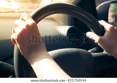 Closeup of woman hands holding steering wheel while Driving Car with sunlight. - stock photo