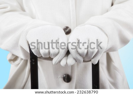 Closeup of woman hands in winter gloves and warm clothes, holding a luggage hand grip - stock photo