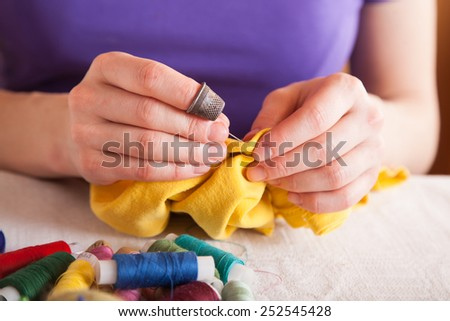 Closeup of woman hands sewing a button. - stock photo