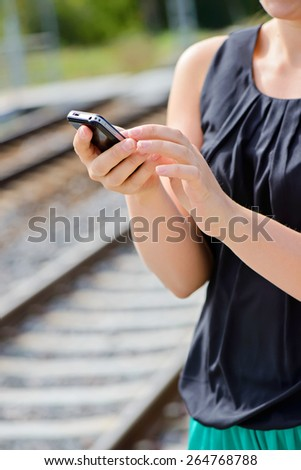 Closeup of woman hands using mobile phone. Shallow depth of field. Focus on the phone and fingers - stock photo