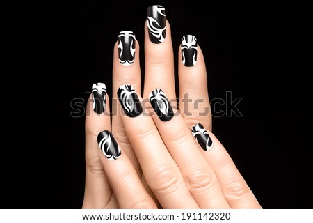 Closeup of woman hands with art nail design. Fashion print nail stickers. Manicure and Nail tattoo - stock photo
