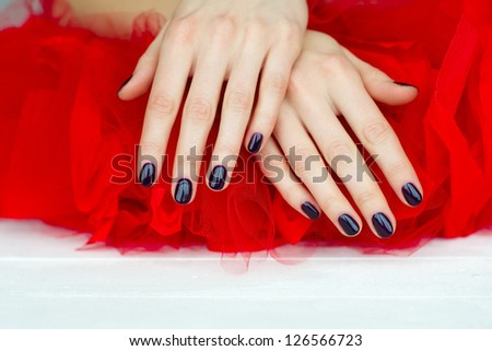 Closeup of woman hands with beautiful dark manicure lying down on red cloth