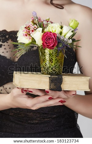 closeup of woman hands with red manicure holding book with black lace and mixed white and red roses bouquet  - stock photo