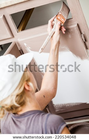 Closeup of Woman Holding Paint Brush and Painting Kitchen Cabinets - stock photo