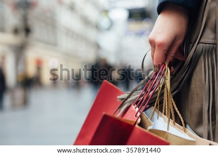 Closeup of woman holding shopping bags on the street with copy space - stock photo
