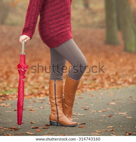Closeup of woman in brown boots with umbrella. Girl in autumn park forest. Fall winter fashion. - stock photo