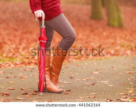 Closeup of woman in brown boots with umbrella. Girl in autumn park forest. Fall winter fashion.