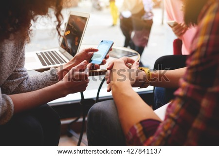 Closeup of woman is reading text message on mobile phone in network, while is sitting with laptop computer in co-working cafe. Group of friends are using gadgets during recreation time in coffee shop