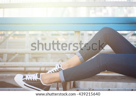 closeup of woman legs in white gumshoes - stock photo