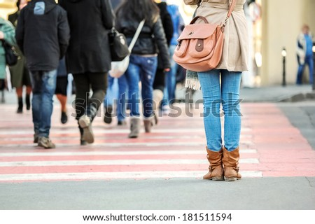 Closeup of woman legs waiting at pedestrian crossing - stock photo