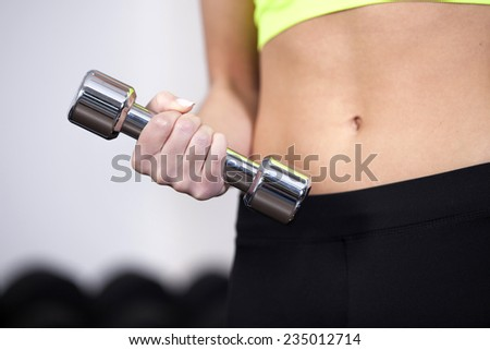 Closeup of woman lifting free weights at the gym - stock photo