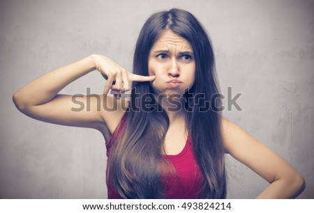 Closeup of woman making funny face on gray background