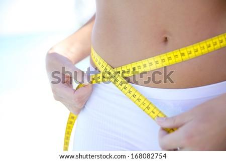 Closeup of woman measuring waist line - stock photo