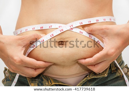 Closeup of woman pinching belly fat, weight loss concept. - stock photo