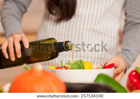 Closeup of woman pouring olive oil into the colorful salad - stock photo