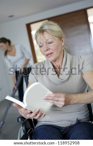 Closeup of woman reading book in wheelchair - stock photo