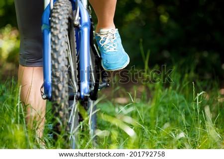 Closeup of woman riding mountain bike outdoors. - stock photo