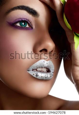 Closeup of woman's face with silver lipstick. Blue contact lenses, purple eye shadows and tanned hand with red metallic and texture manicure holding red fabric flower - stock photo