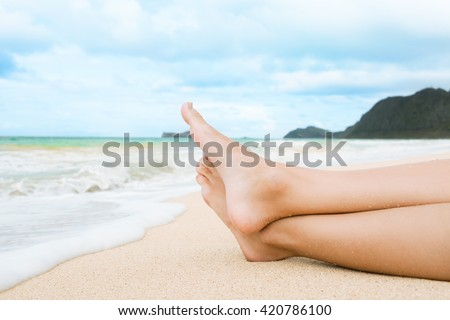Closeup of woman's feet relaxing on a tropical beach in Hawaii.  - stock photo