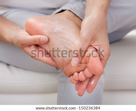 Closeup of woman's hand applying cream on feet - stock photo