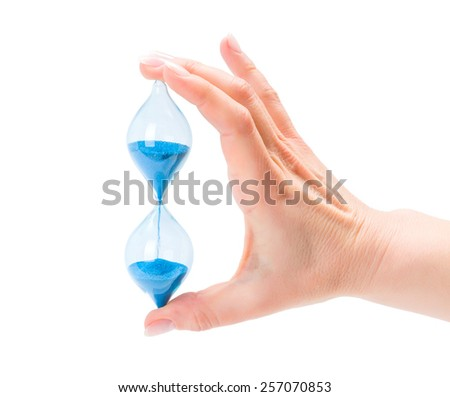 Closeup of woman's hand holding sand hourglass isolated on white