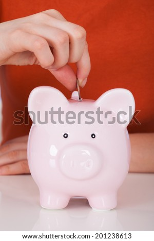 Closeup of woman's hand inserting coin in piggybank