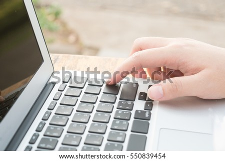 Closeup of woman's  hand on laptop keyboard . Working , shopping online concept