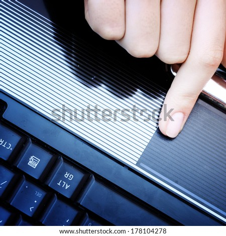 Closeup of woman's hand working at laptop.