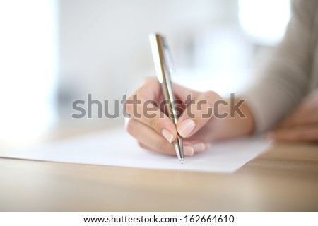Closeup of woman's hand writing on paper - stock photo
