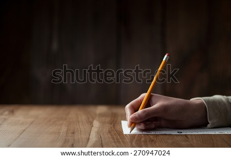 Closeup of woman's hand writing on paper over wooden table - stock photo