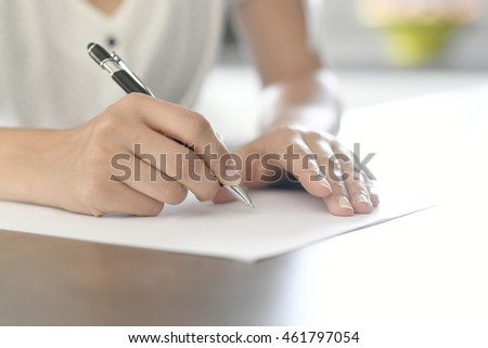 Closeup of woman's hand writing on paper with pen