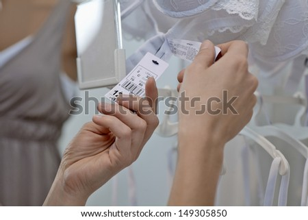 Closeup of woman's hands holding clothes tag attached to bra in store - stock photo