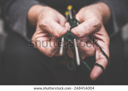 closeup of woman's hands holding knitting needles and string