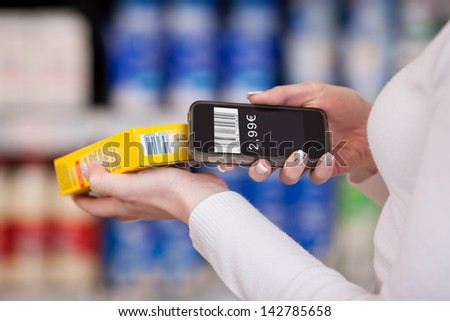 Closeup of woman's hands scanning barcode with mobile phone in supermarket - stock photo