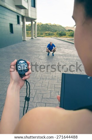 Closeup of woman trainer hand using a chronometer to timing at tired athletic man in a hard training outdoors - stock photo