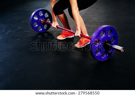 Closeup of woman training deadlift at gym. Weightlifting workout - stock photo