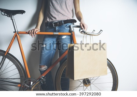 Closeup of woman wearing blue jeans and standing with vintage orange bike and blank paper package, mock-up of craft shopping bag with handles - stock photo