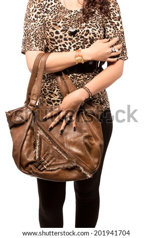 Closeup of woman with brown leather and fur bag wearing black tights and leopard top. Isolated on the white studio background