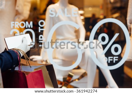 Closeup of woman with shopping bags and mobile phone in front of showcase boutiques. Discount from 30 up to 60 percent. - stock photo