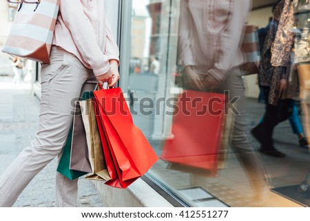 Closeup of woman with shopping bags looking at boutique showcase with copy space