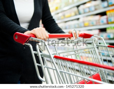 Closeup of woman with shopping cart. - stock photo