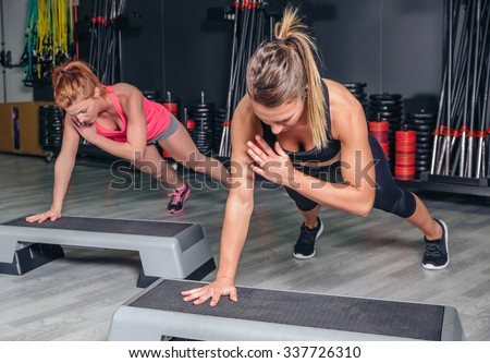 Closeup of women couple training hard over steppers in aerobic class on a fitness center. Sport and health concept. - stock photo