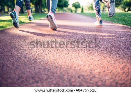 Closeup of women running on a jogging track in the park, empty space for your ad